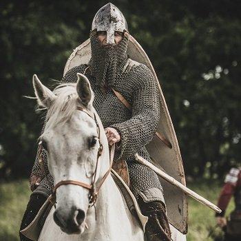 Jeździec - słowiański rycerz w zbroi na białym koniu.